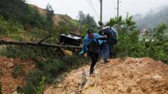 Men cross a mudslide blocking a road after the passage of Storm Eta, in Purulha, Baja Verapa