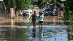 Couple wade through flooded street in La Lima, Honduras, on 8 November 2020