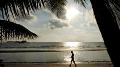 A person walks along the beach on Koh Chang Island in Trat province, 350 kms south of Bangkok during sunset