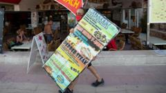 A waiter carries a sign in Magaluf
