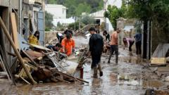 Locals remove debris on a street covered with muddy water in Sant Llorenc des Cardassar, on the Spanish Balearic island of Majorca