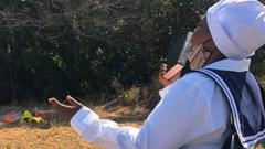A woman praying at the site of where one of the victims was found in Mthwalume, South Africa
