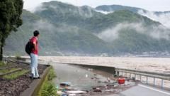A man looks at the overflowing Kuma river in Yatsushiro, Kumamoto prefecture, 4 July