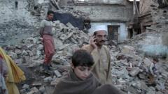 People looking at damaged houses in Afghanistan