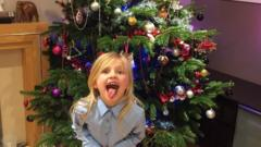 A girl in front of a Christmas tree