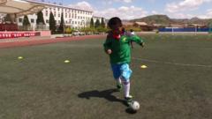 A Chinese boy playing football.
