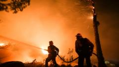 Firefighters battle a wildfire as it burns along a hillside near homes in Santa Paula, California, on December 5, 2017. Fast-moving, wind-fueled brush fire exploded to about 10,000 acres in Ventura County Monday night, forcing hundreds of people to flee their homes, officials said