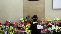 A police officer looks at flowers left at Kings Cross Underground station to remember 7/7 victims
