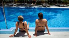 German tourists sit at a swimming pool in Majorca