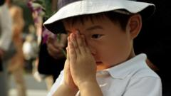 A boy prays for the atomic bomb victims in front of the cenotaph at the Hiroshima Peace Memorial Park in Hiroshima, western Japan, early Thursday, Aug. 6, 2015. Japan marked the 70th anniversary of the atomic bombing on Hiroshima.