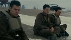 Harry Styles in Dunkirk Movie. He is sitting with co-stars on the beach.