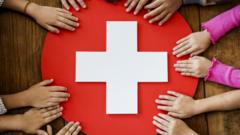kids holding onto red cross sign