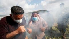 Palestinian demonstrators react to tear gas fired by Israeli troops during a protest against Israeli settlements
