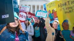 Demonstrators shout slogans and hold banners in an abortion rights rally outside of the Supreme Court