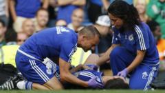 Head Physio Jon Fearn and club doctor Eva Carneiro treating Eden Hazard