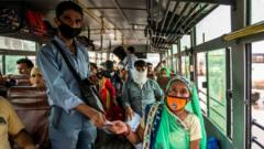 A bus conductor issues tickets to a female passenger in Uttar Pradesh.