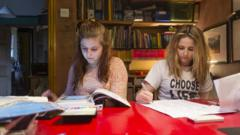 2 girls sitting at a desk doing homework