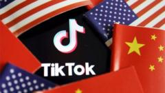 The TikTok logo is seen here partly covered by a ring of alternating US and Chinese flags