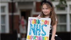 Girl holds sign saying thank you nhs and my mummy