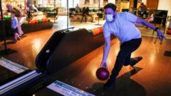 Man in face mask bowling