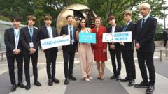 BTS-UNICEF-stand-together-in-front-of-a-sculpture.