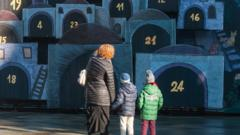 A woman and two children looking at a large advent calendar