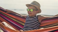 Young boy wearing sunglasses and a hat - chilling out on a hammock