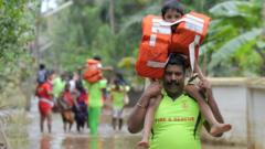 A fire & rescue worker carries a child on his shoulders away from the flood area