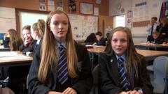 Two school pupils sat next to each other
