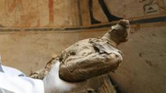 An archaeologist holding a mummified falcon