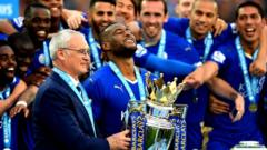 Leicester City captain Wes Morgan and manager Claudio Ranieri lifting the Premier League trophy together.