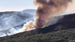 Helicopter dropping water over wildfire
