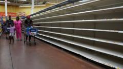 People walk past empty shelves in store