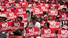 Protesters hold placards and shout slogans during a rally against the extradition law proposal