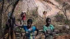 Women workers wait at a colbalt mine