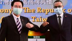 Mohamed Hagi (R), Somaliland's Taiwan representative, bumps elbows while posing with Taiwan's Foreign Minister Joseph Wu during the opening ceremony of the Somaliland representative office in Taipei on September 9, 2020