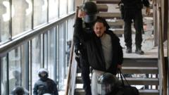 Spanish rapper Pablo Hasel reacts as he is detained by riot police inside the University of Lleida