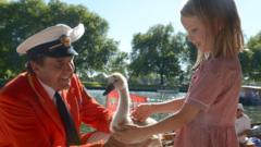 Swan Marker David Barber shows Neave a young swan called a cygnet during the annual Swan Upping on the River Thames.