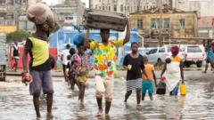 People carry their personal effects through a flooded section of Praia Nova, Beira,