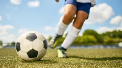 childs-legs-kicking-football