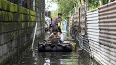 Children use a raft to cross a flooded alley in the aftermath of Super Typhoon Mangkhut