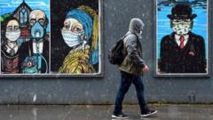pedestrian-walks-past-paintings-wearing-masks-in-glasgow