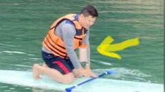 Mr Chen paddleboarding with his phone hung on a lanyard
