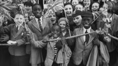 Children line up in Brixton waving union jacks as Queen Mary visits to open Lambeth Town Hall, 1938