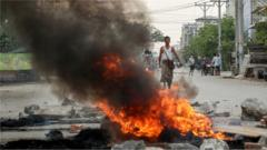 A demonstrator looks on along burning debris during a protest against the military coup in Mandalay, Myanmar, 21 March 2021.