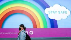 """A woman wearing a face mask walks past a rainbow poster with a message to """"Stay Safe"""""""
