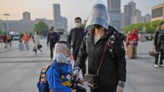 mother-and-son-wearing-masks-prepare-to-leave-wuhan