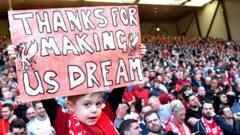 young-fan-holds-up-liverpool-sign.