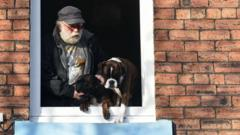 These two dogs and their owner look out of the window as they wait to be rescued in Carlisle.