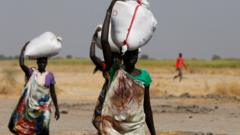 Women carrying sacks of food in South Sudan
